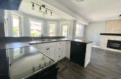 kitchen showing fireplace, double sink and large windows